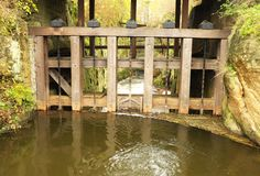 Water of small river flow at historical wooden weir. Terrible smell water with bubbles and reflection. Stony walls of weir Stock Photos