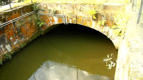 Water of small river flow into small stony tunnel or bridge. Green muddy water with shadows and reflection.. stock video
