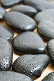 Water on smooth black stones Royalty Free Stock Image