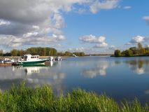 Water smooth surface of the river Kotorosl with reflecting clouds, pier with motorboats, Yaroslavl Stock Photography