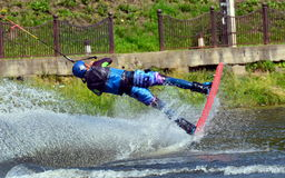 Water snowboard. The athlete with snowboard hold on to the rope and the boat accelerates Stock Image