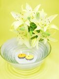 Water for spa with lily bunch. Clean water for spa with lily bouquet on yellow background Stock Photo