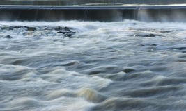 Water spillover. A dam with water spilling over and creating rapids Stock Photo