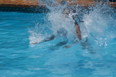 Water Splash. Es out the pool, as the swimmer dives in Royalty Free Stock Photography