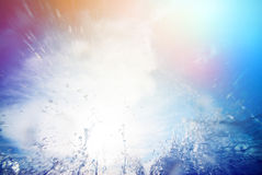 Water splash against the sky and the sun Royalty Free Stock Photo