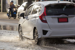 Water splash with car on flooded road after rains.  Stock Images