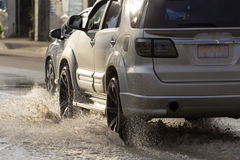 Water splash with car on flooded road after rains.  Royalty Free Stock Images