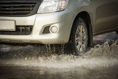 Water splash with car on flooded road after rains.  Royalty Free Stock Photos