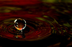 Water splash in color with a drop of water. Flying from above stock photo