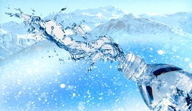 Water splashes from plastic water bottle, beautiful snowy mountain on back ground royalty free stock photography