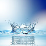 Water splash in dark blue color with a drop of water flying from above Royalty Free Stock Photo
