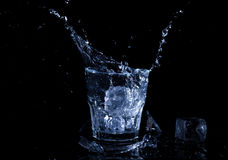 Water splash in a glass. A glass of cold water. Cold water with ice Royalty Free Stock Photos