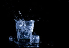 Water splash in a glass. A glass of cold water. Cold water with ice Royalty Free Stock Images
