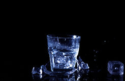 Water splash in a glass. A glass of cold water. Cold water with ice.  Stock Photos