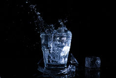 Water splash in a glass. A glass of cold water. Cold water with ice.  Royalty Free Stock Photos