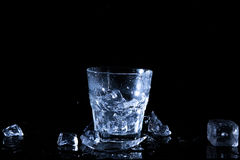 Water splash in a glass. A glass of cold water. Cold water with ice.  Royalty Free Stock Photography