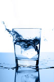 Water splash in glass with ice Stock Image