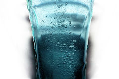 Water splash in Glass. Water is released in a drinking glass with pressure Royalty Free Stock Photo