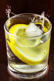Water splash in glasses with lemon slice and ice cube, on wooden table Royalty Free Stock Image