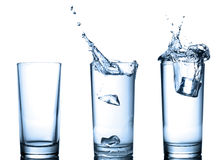 Water splash in glasses  on white Stock Photos