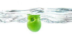 Water splash. Green apple under water. Air bubble and transparen Stock Photos