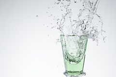 Water splash in green drinking glass Stock Images
