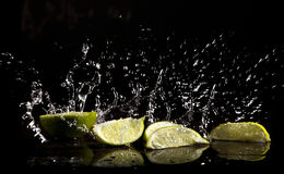 Water splash and limes Stock Photos