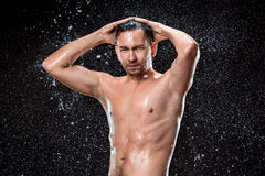 The water splash on male face. And naked torso against black background Royalty Free Stock Photo