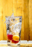 Water splash over glass. Apricot drink Stock Images
