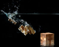 Water splash with puzzle effect. Water splash with puzzle falling in water. The concept of collecting a whole from parts Royalty Free Stock Photos