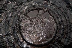 Water splash from rain drop over the black cap in black and whit. E high contrast Stock Photos