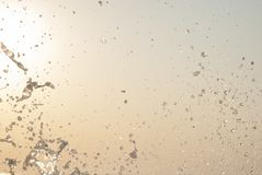 Water splash at the seaside - droplets in the sun. Sea water splash - droplets in the sun on a clear sky Stock Photo