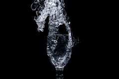 Water Splash Series - Mini Wine Glass Flare. Image showing water splashing from a mini wine glass as it`s being poured into it. Solid black background with stock photos