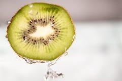 Water splash on sliced kiwi fruit Royalty Free Stock Photo