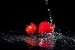 Water Splash on Strawberries. Two strawberries with water poured over them making water splashes Royalty Free Stock Photography
