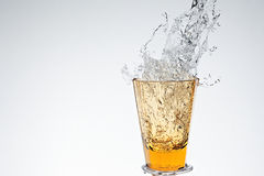 Water splash in yellow drinking glass Royalty Free Stock Images