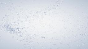 Water splashes. In the air on blue background stock footage