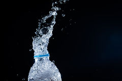 The Water splashes from the bottle on black background Stock Images