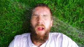 Water splashes in face of bearded man stock video