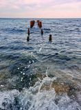 Seascape with splashes and old poles. Water splashes and an old poles in the sea Royalty Free Stock Images