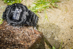 Water splashes on a rugged wristwatch royalty free stock images