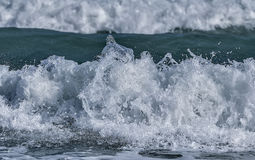 Water splashes on sea/ocean wave crest against blurred bac. Sharp water splashes on sea/ocean wave crest against blurred background royalty free stock photos