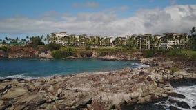 Water splashing against stones on the background of fairy resort montage kapalua on maui,hawaii stock video footage