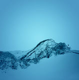 Water splashing on blue Stock Images