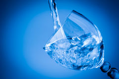 Water splashing in a blue glass Stock Photos