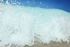 Water splashing.  Blue sky above the beach in the sun zenith ref. Stormy sea. Splashes and waves on the background of rocks Royalty Free Stock Photos