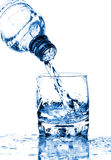 Water splashing from bottle into glass Royalty Free Stock Images