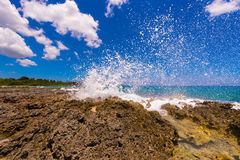 Water splashing - crystal clear sea water beating against the rocks. In Bayahibe, La Altagracia, Dominican Republic. Close-up. Stock Photography