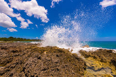 Water splashing - crystal clear sea water beating against the rocks. In Bayahibe, La Altagracia, Dominican Republic. Copy space for text stock image