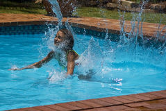 Water Splashing Dive. Water splashes out the pool, as the child dives in Royalty Free Stock Images